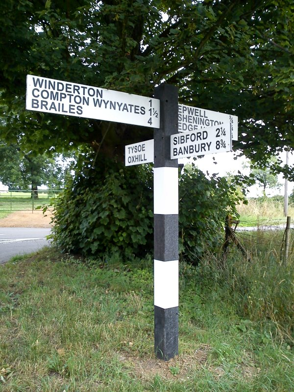 A black and white striped sign post with perpendicular signs