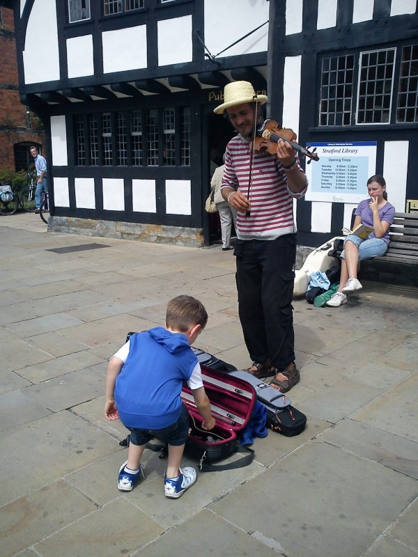 A busker playing a violin and a little boy bending down to put change into the violin case