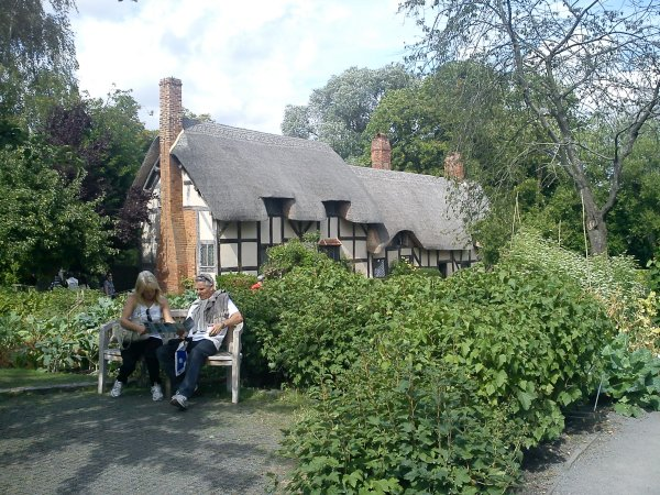 Two people sit on a bench outside the garden of a thatch-roofed cottage