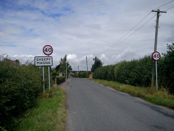 Road with signpost to the left reading 'Sheepy Magna'