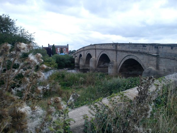 A stone arched bridge over a river