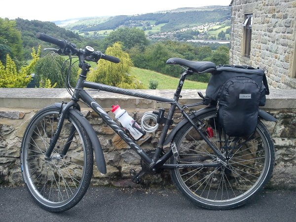 Photo of my bike leant against a stone wall and hills in the background