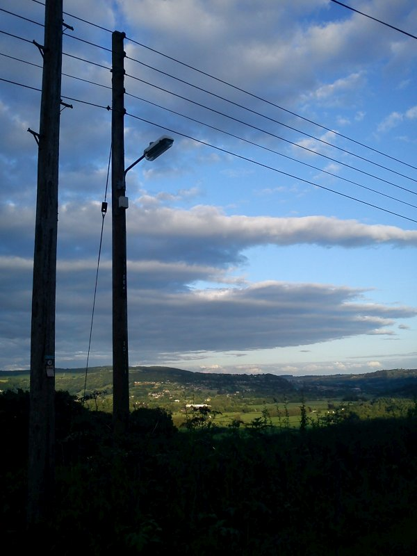 Telephone pole with lamp attached (off) in silhouette against the sky and hills